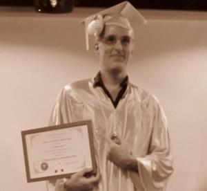 A/P Wyse holds up his tenure scroll, while balancing that Hello Kitty on his mortarboard.