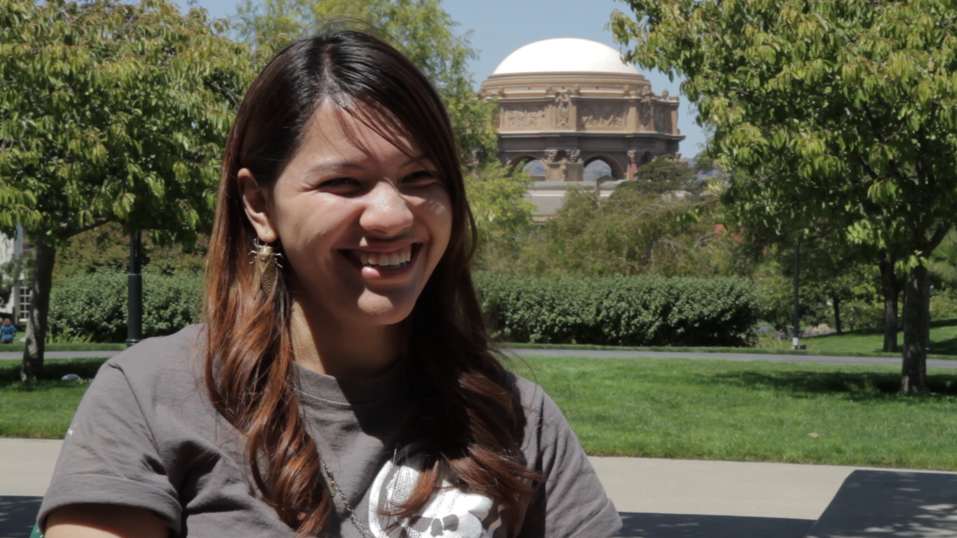 Female intern wearing a brown t-shirt stands in front of the Palace of Fine Arts